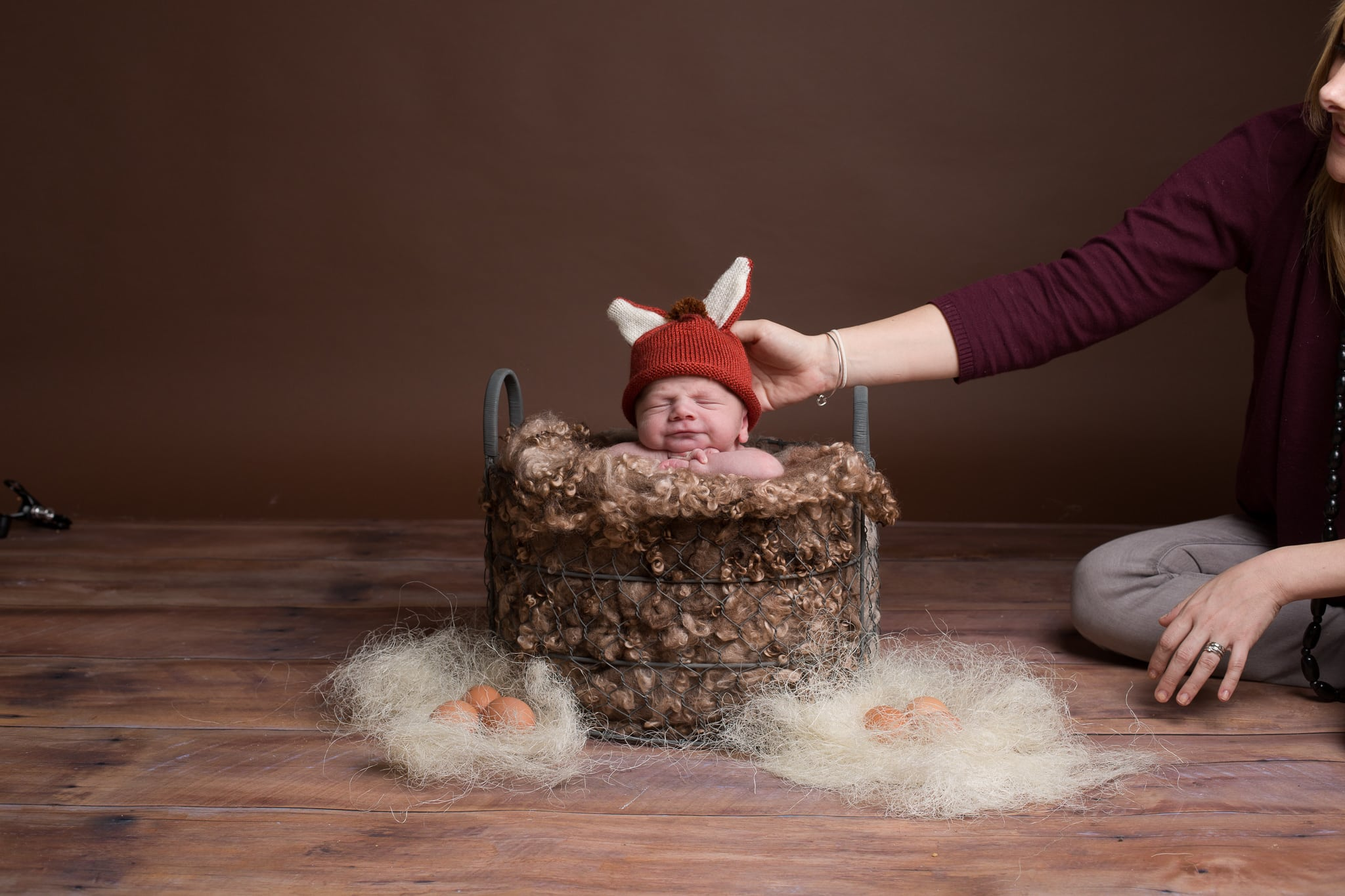 baby being held in a basket