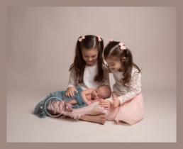 sister cuddle newborn baby brother