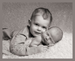 older brother cuddling his newborn baby sibling