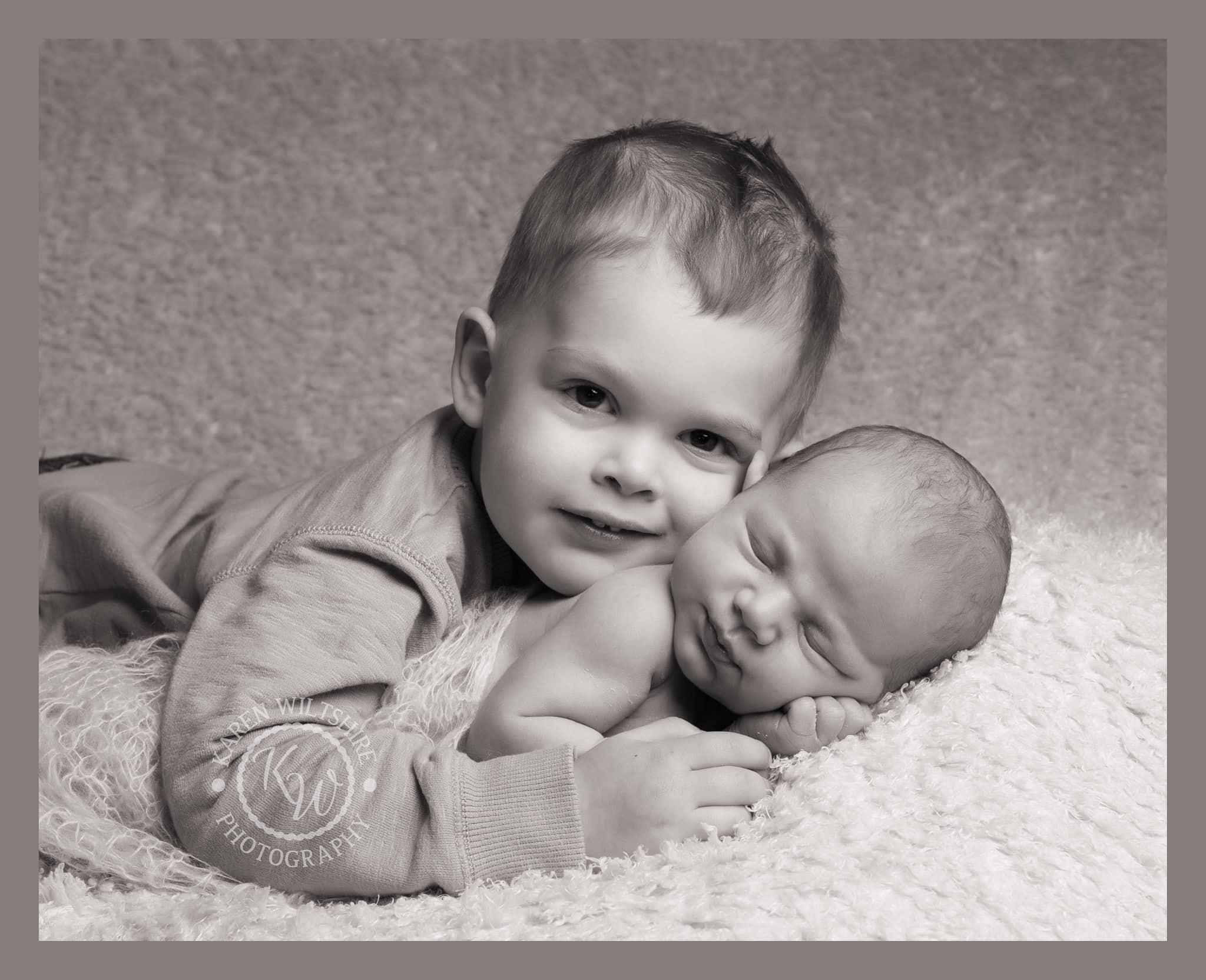 older brother cuddling his newborn baby sibling