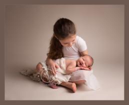 older sibling holding newborn baby