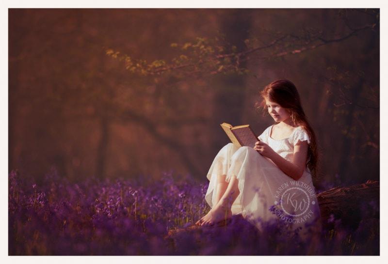 Girl reading in bluebell woods