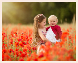 Sisters in field of red poppies