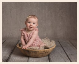 Cute sitting baby girl in wooded bowl