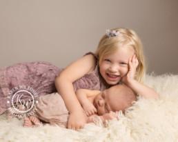 Older sister cuddling newborn baby