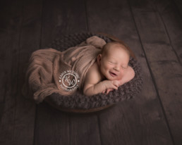 newborn baby boy smiling