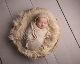 sleeping newborn baby in bowl