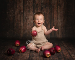 Baby Photographer Bournemouth, baby boy sitting on floor surrounded by apples