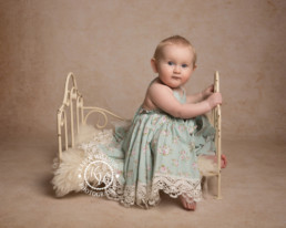 baby in floral dress sitting on metal bed, children & baby photography poole dorset