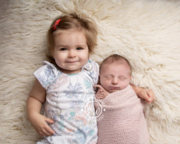 Baby sister in older sisters arms