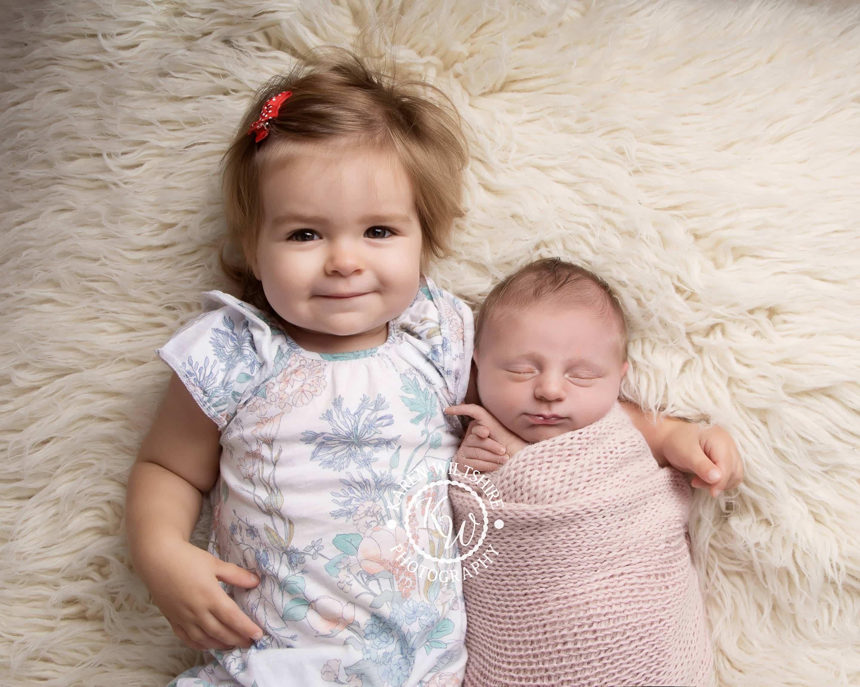 Baby sister in older sisters arms