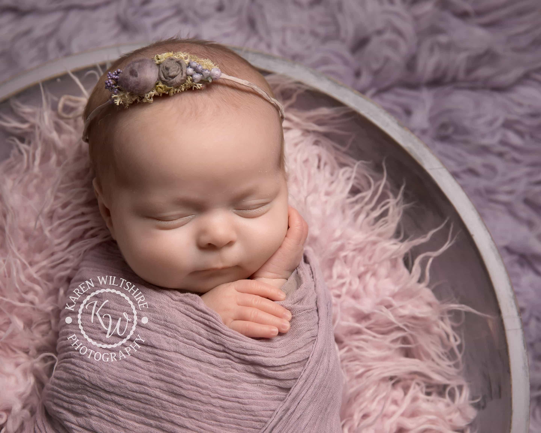 Newborn baby girl in a lavender coloured fur throw