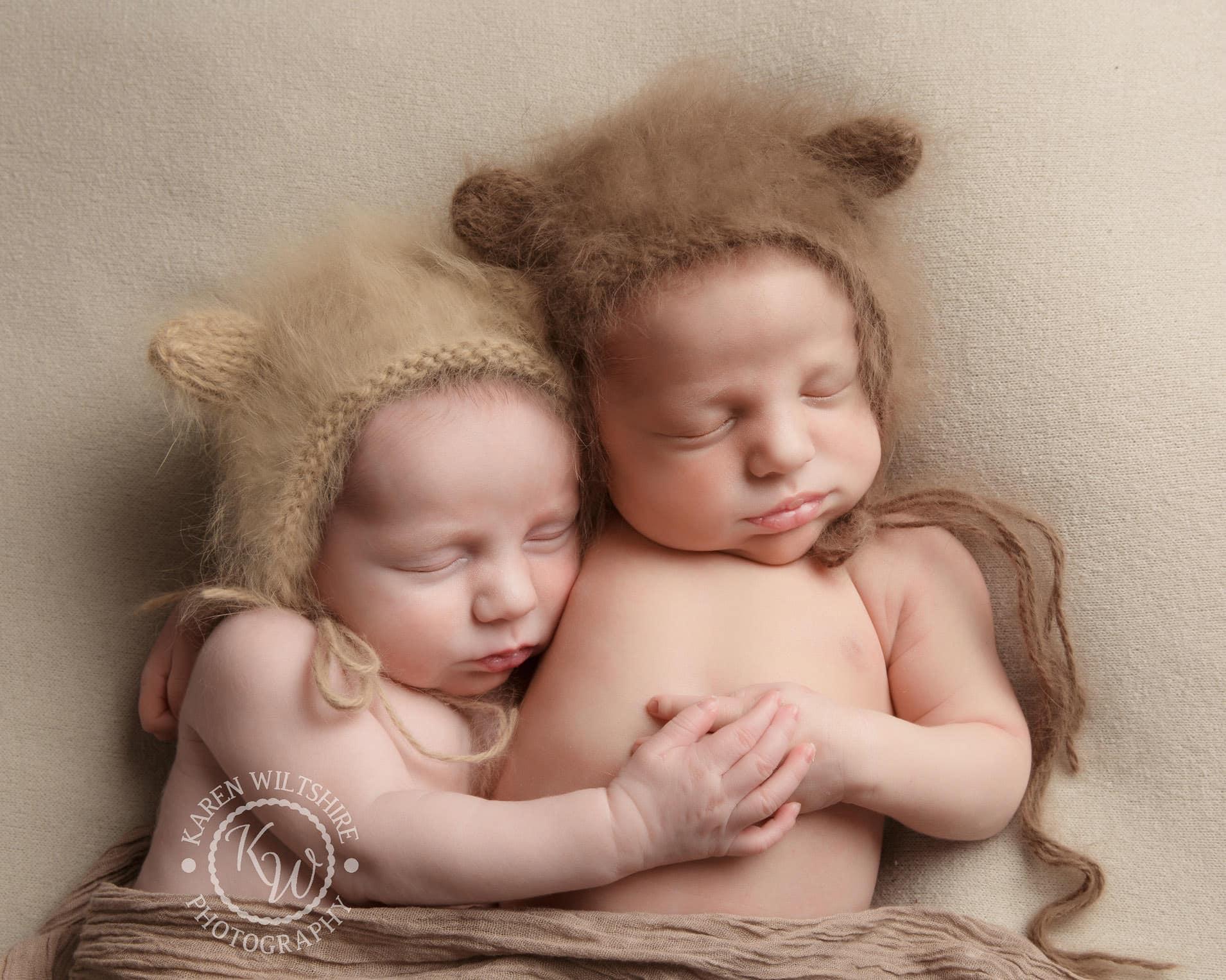 Newborn twins holding hands