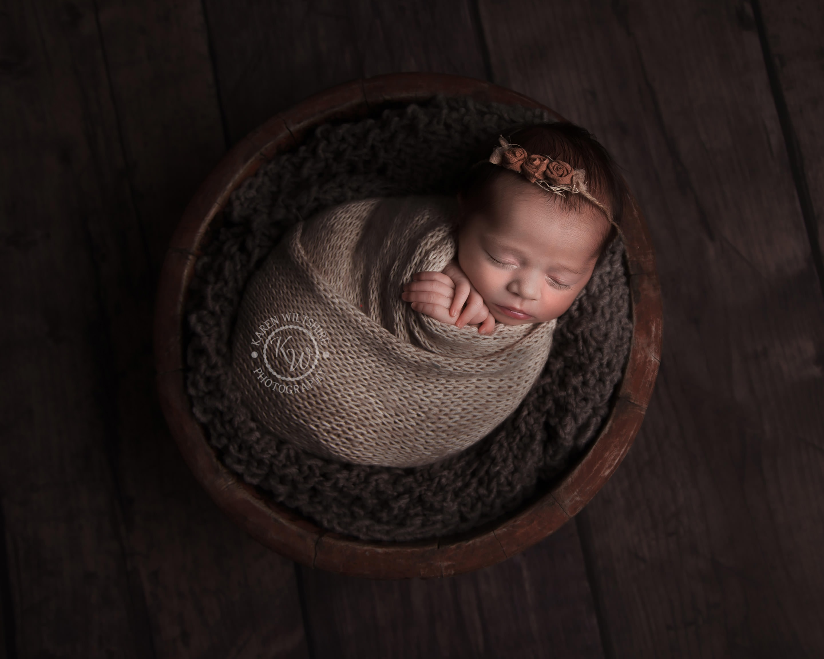 Newborn baby in brown wrap and headband placed in a bowl for newborn photos