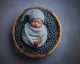 Newborn Baby curled up in a bowl