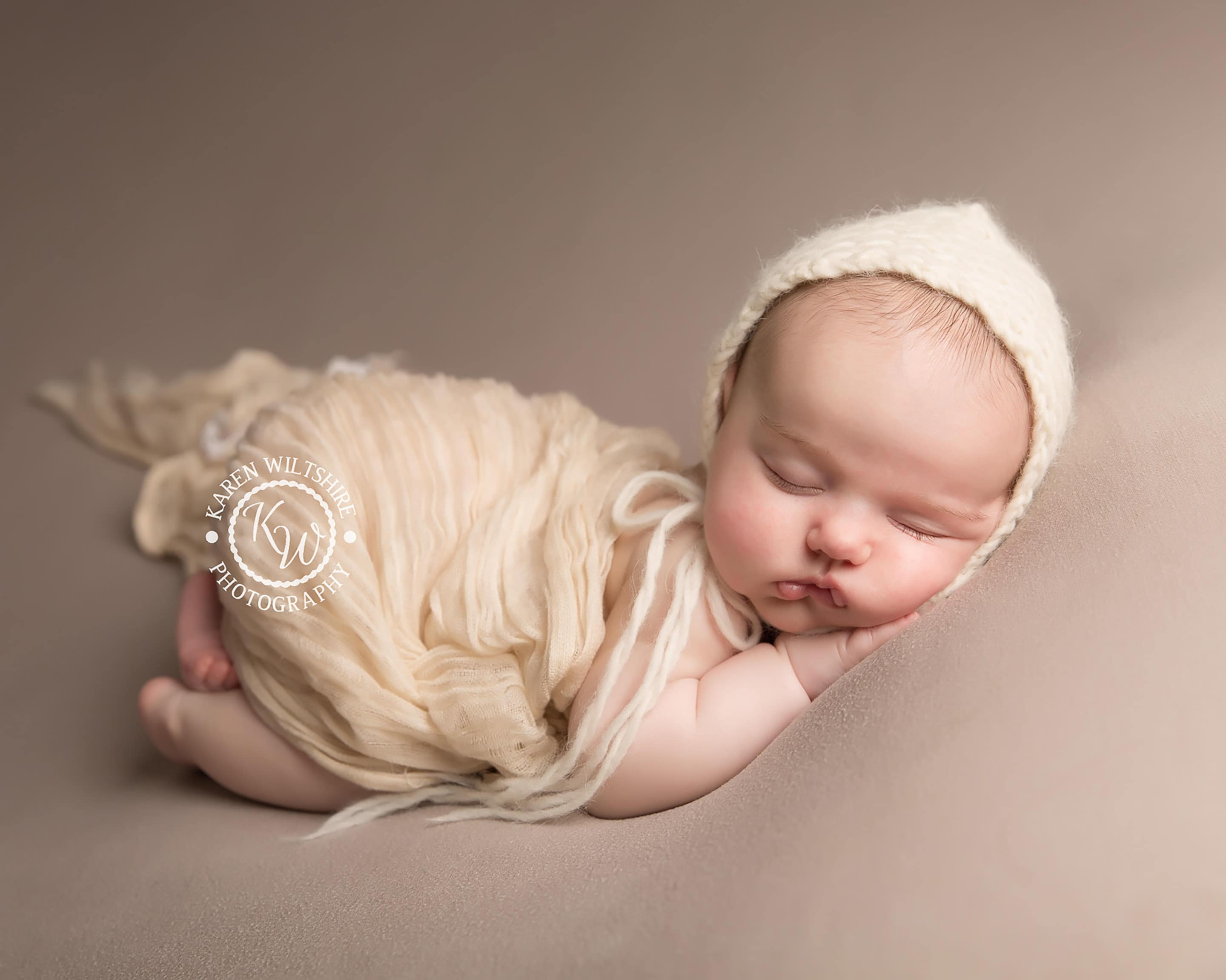 Older newborn baby girl on her tummy in a cream wrap and hat