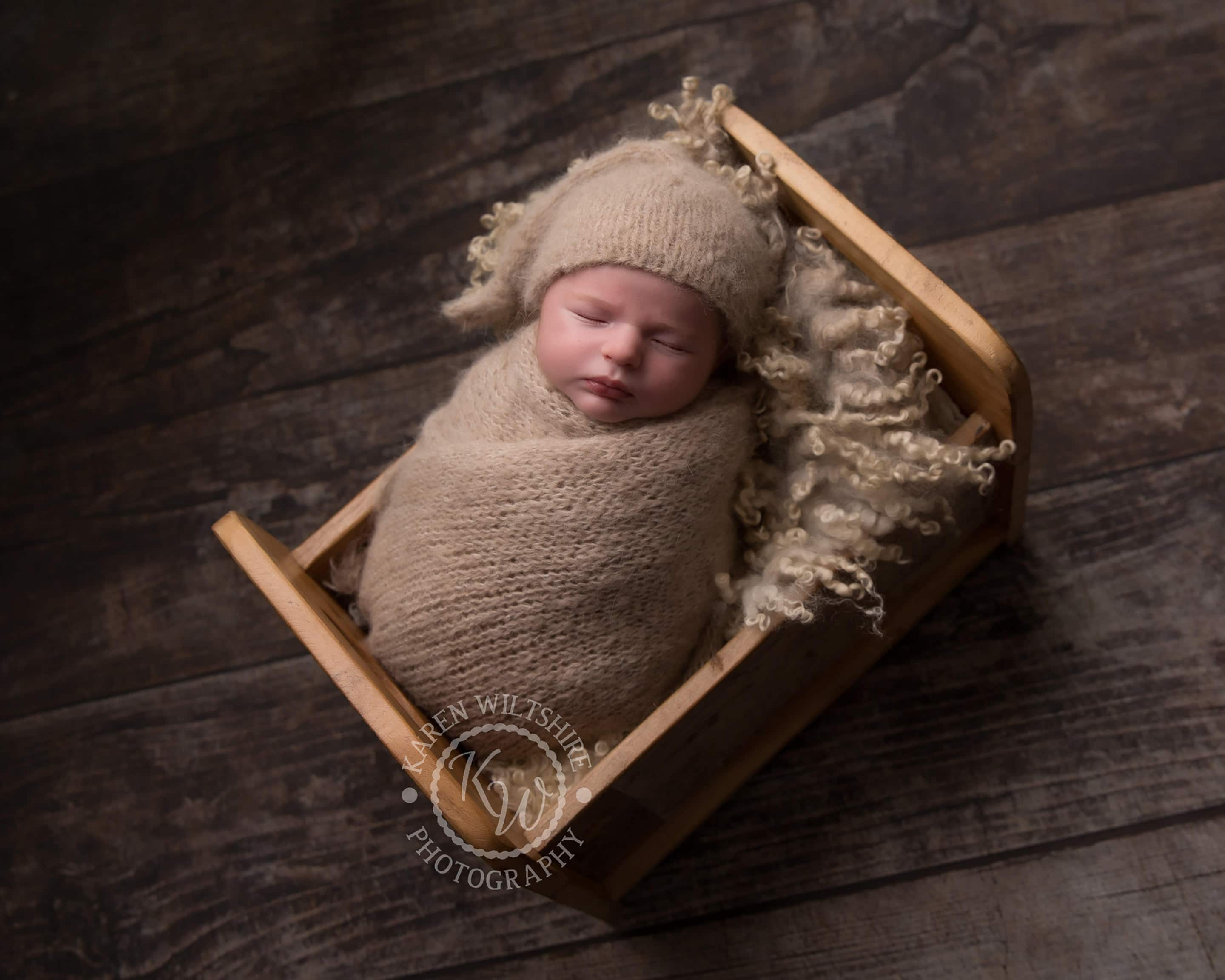 Baby boy in neutral brown wrap and hat in a small wooden bed