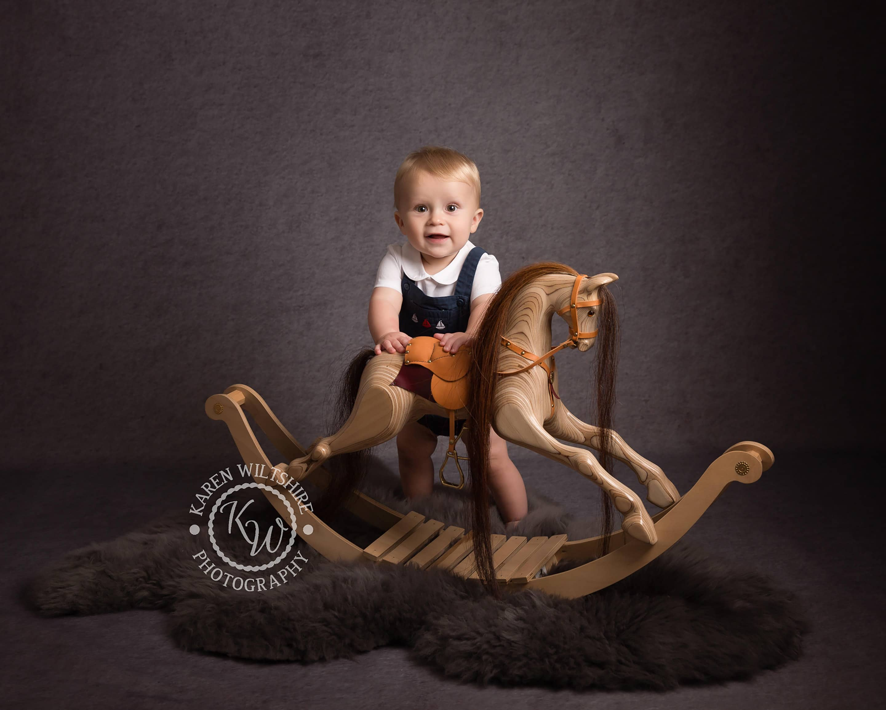 boy playing with wooden rocking horse