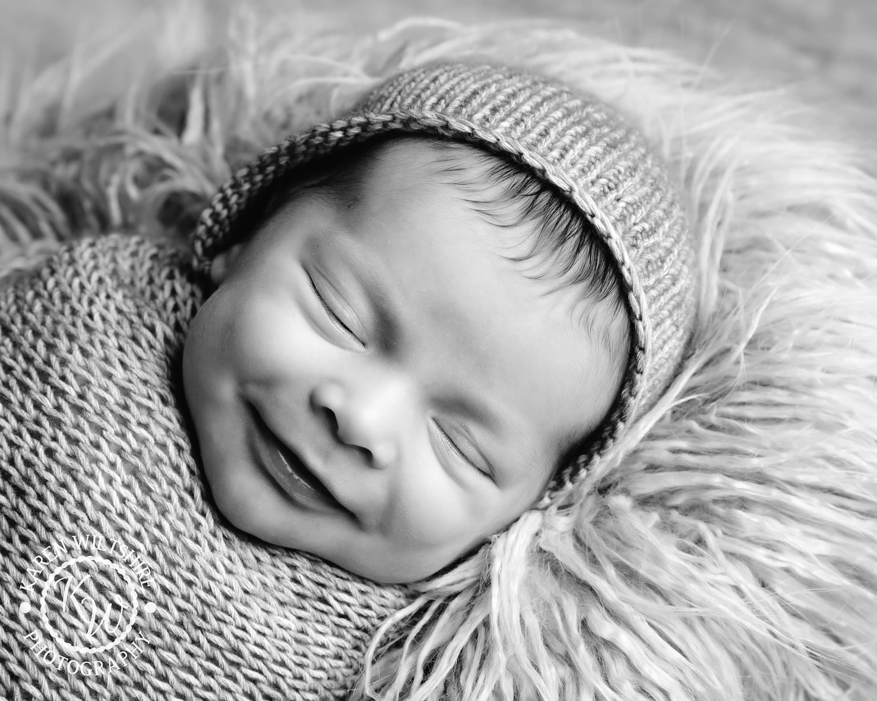 baby in hat smiling for camera