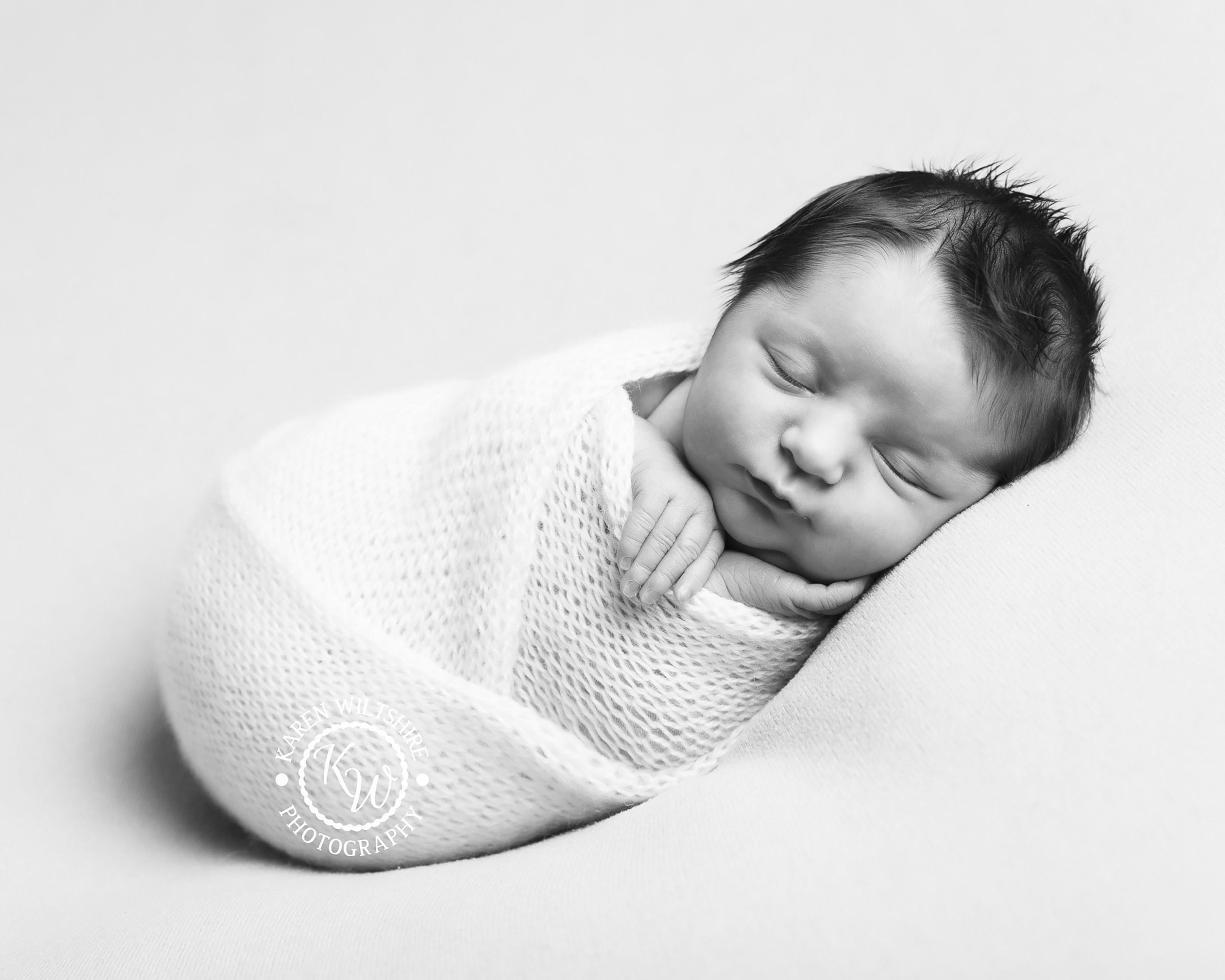 Newborn baby wrapped in white knitted blanket