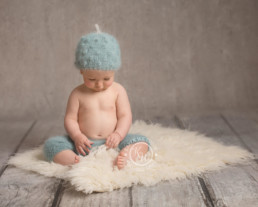 Cute Baby boy sitting on a fur rug at children & baby photography poole dorset