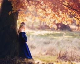 Pregnant lady in blue velvet dress under a tree