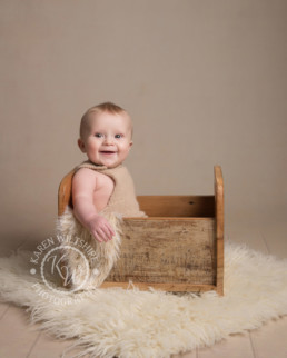 Baby Photography Poole , baby boy sitting in a wooden crate