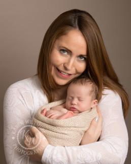 New mum, cuddling her newborn baby