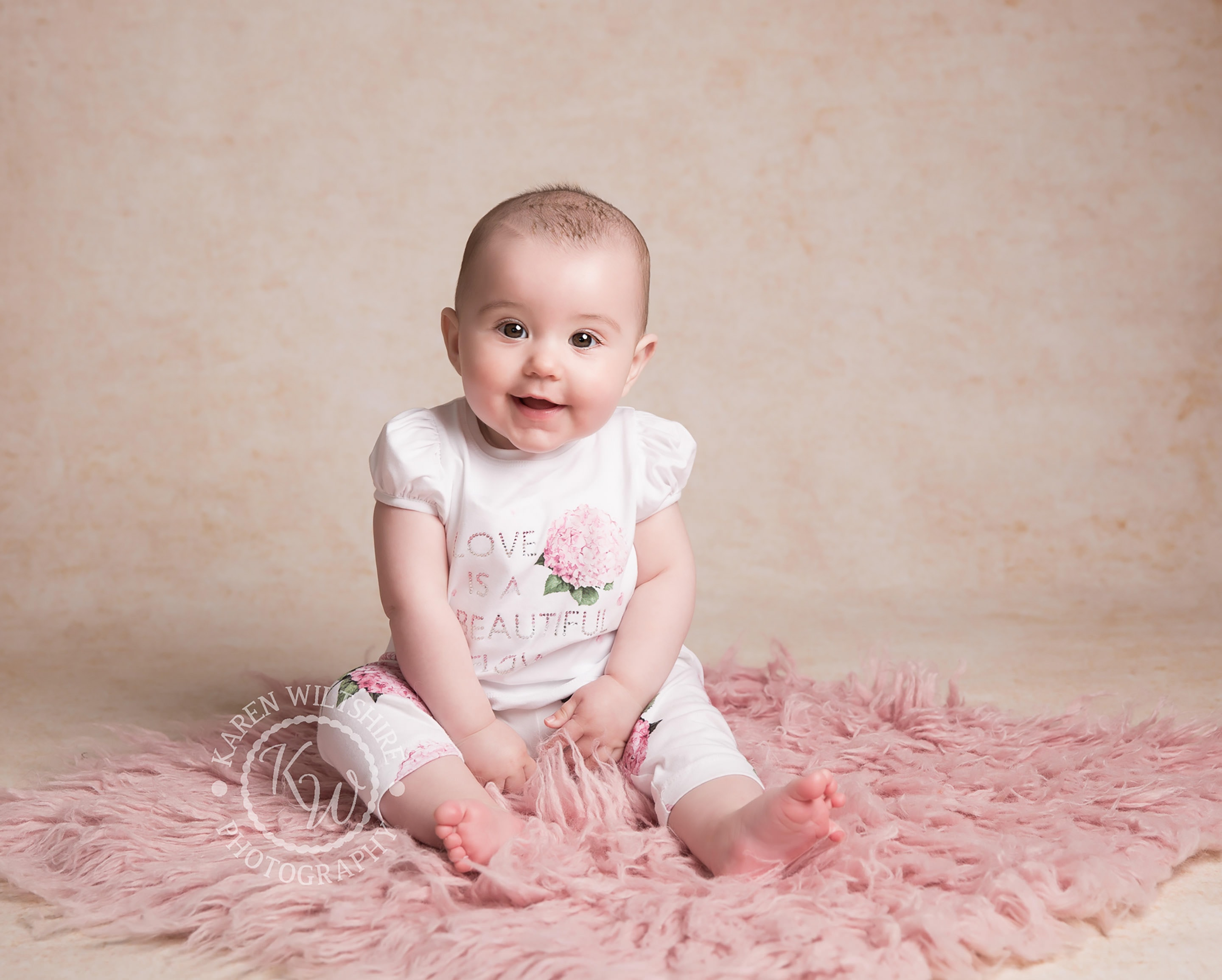 baby photographer Dorset, girl sitting on pink rug and smiling
