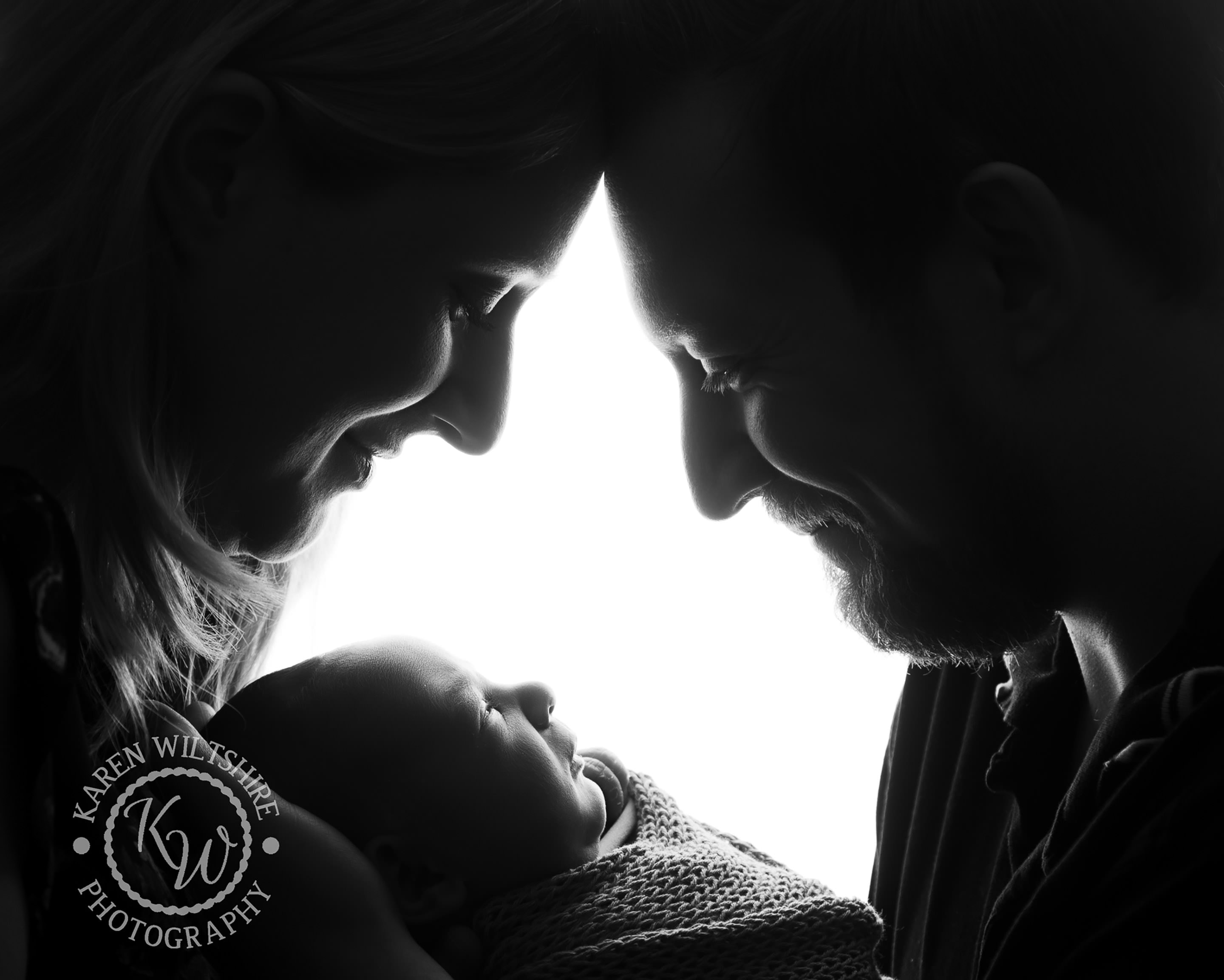 Parent of newborn baby boy smiling down at the baby