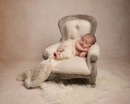 Newborn baby laying in a tiny arm chair
