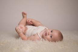 baby boy laying on a cream rug