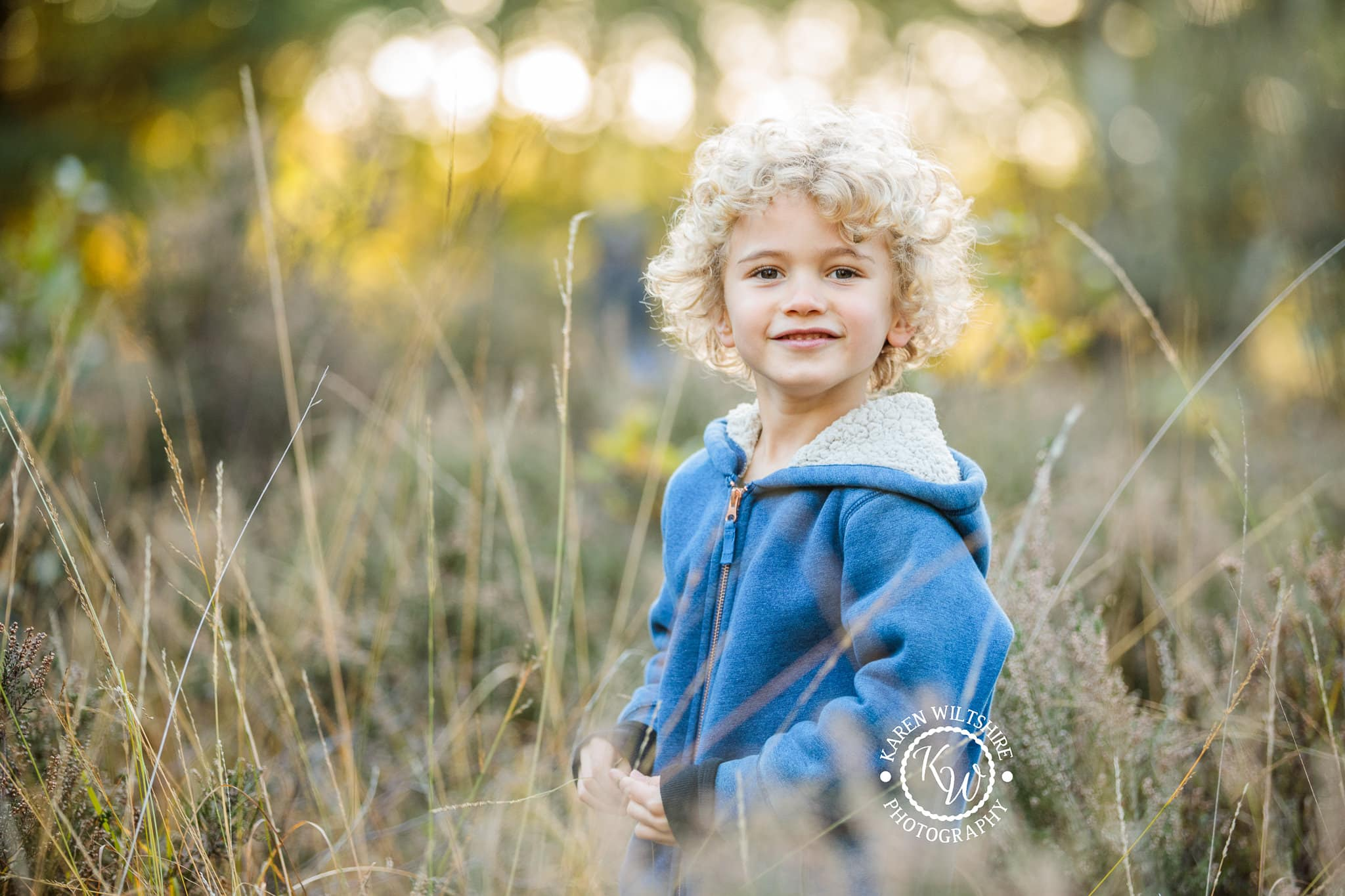 Young boy in long grass smiling for the camera