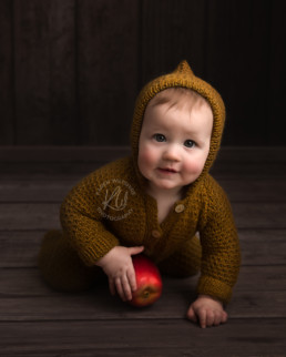 baby boy in knitted romper holding and apple