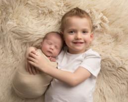 older brother cudling newborn baby sister