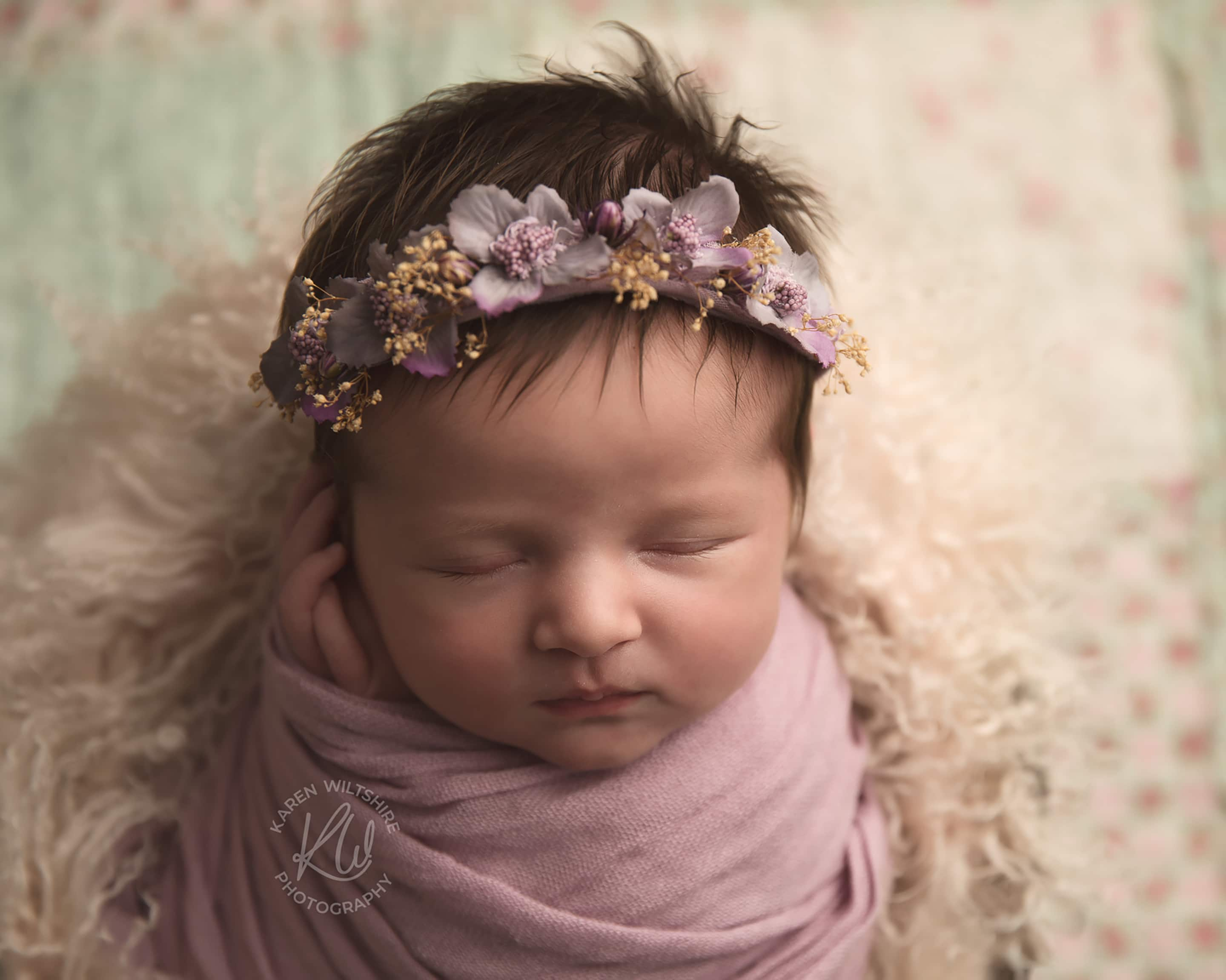 Newborn baby with lots of hair wearing a flower crown