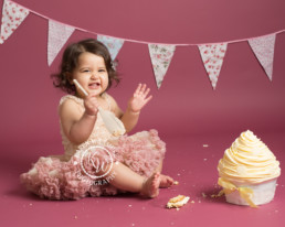 Baby girl in tutu smashing cake