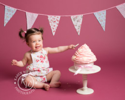 Baby smashes cake for first birthday photo