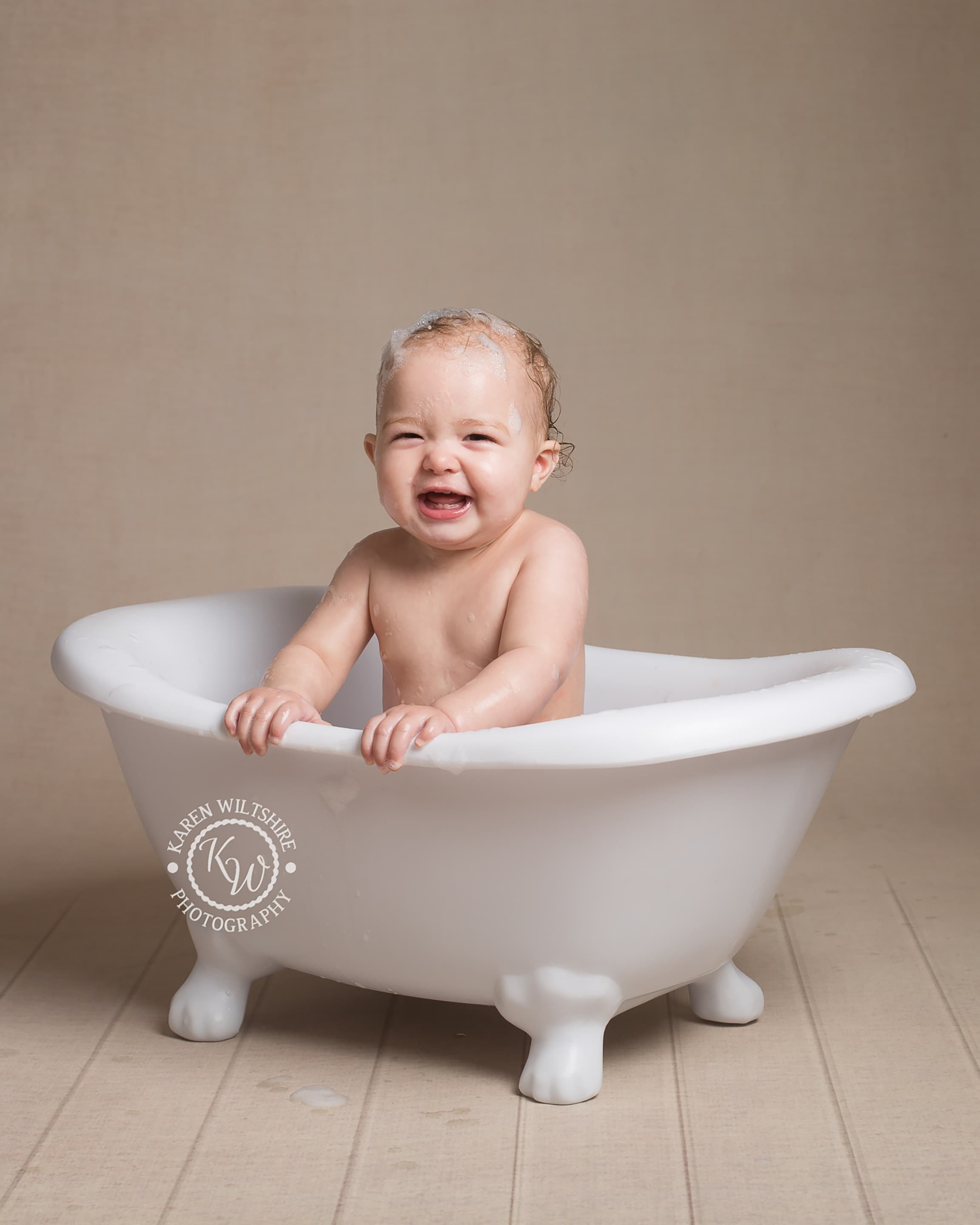 Baby in cute miniature roll top bath