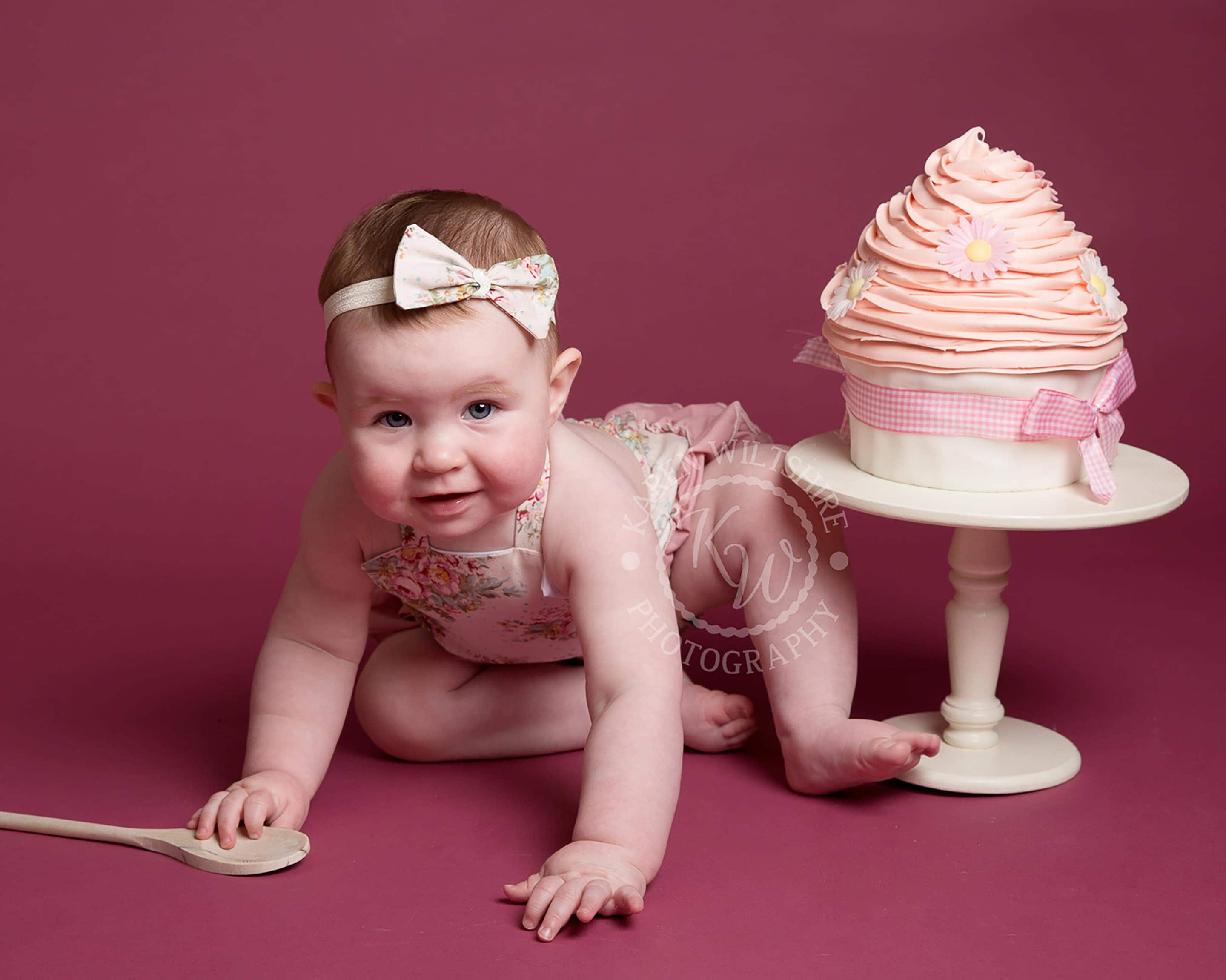 baby girl in pink romper and bow headband enjoying cake smash