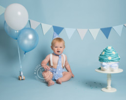 baby boy celebrates first birthday with a cake smash photoshoot