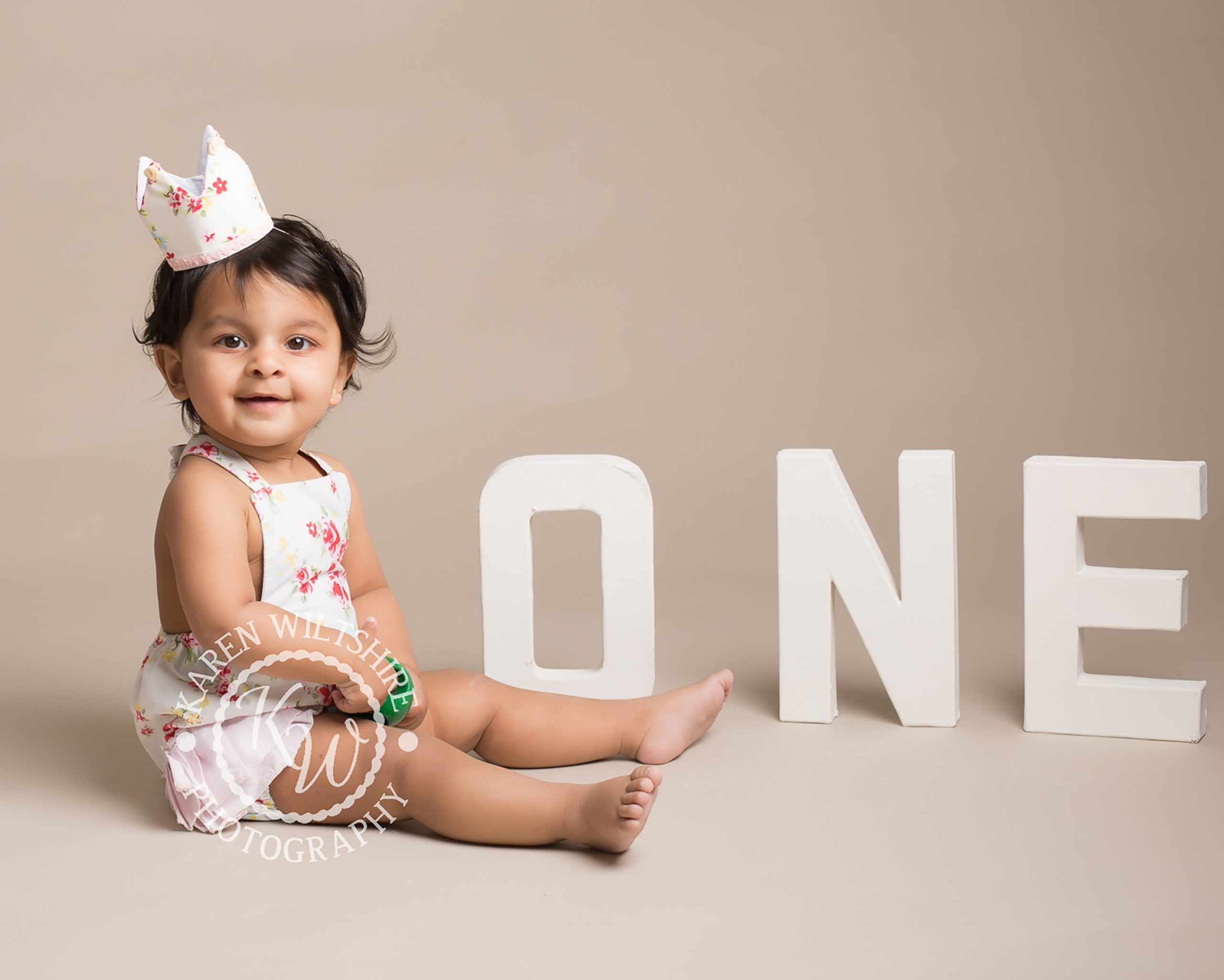 Baby girl poses next the ONE letters