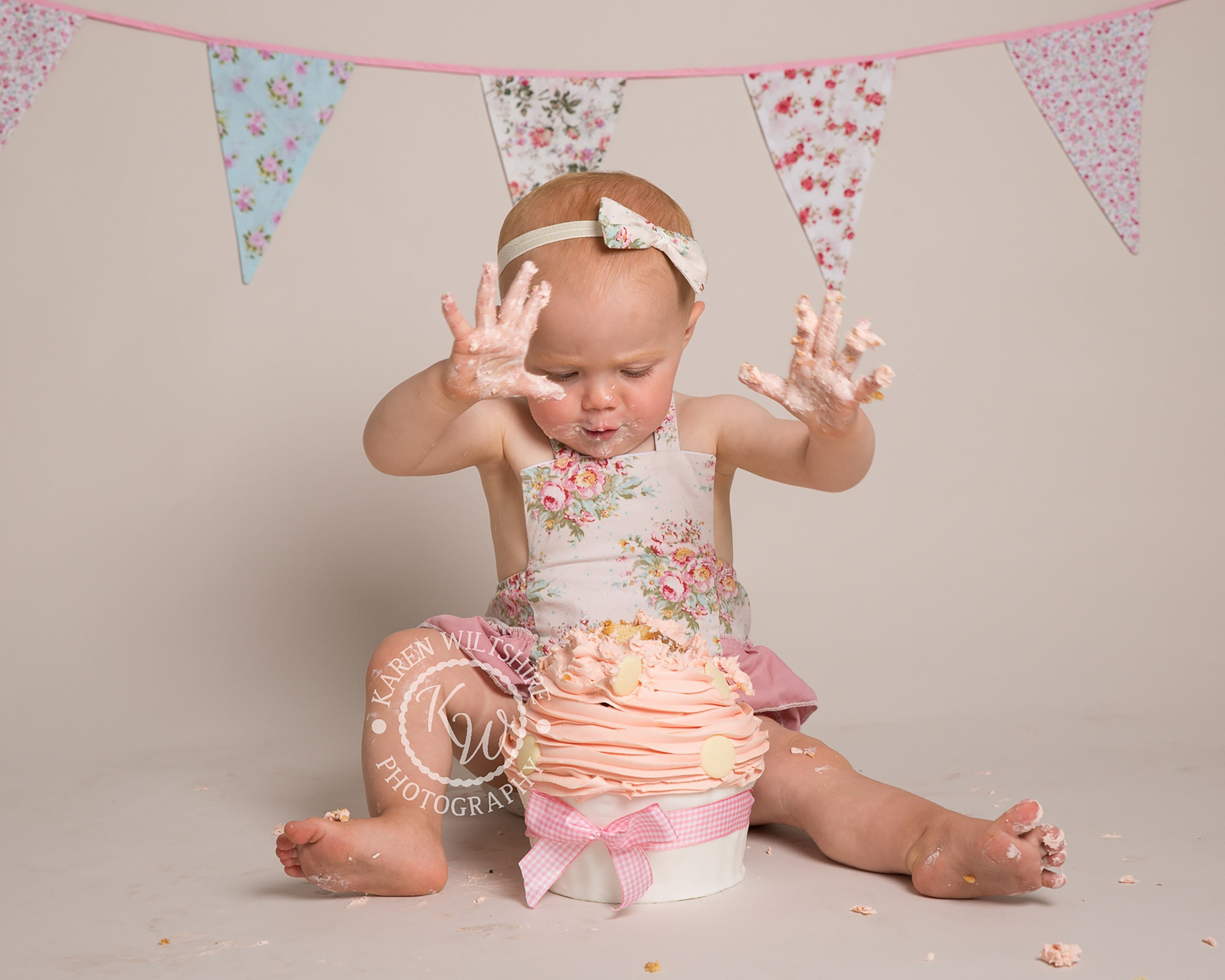 baby girl plunges hands into a giant cup cake