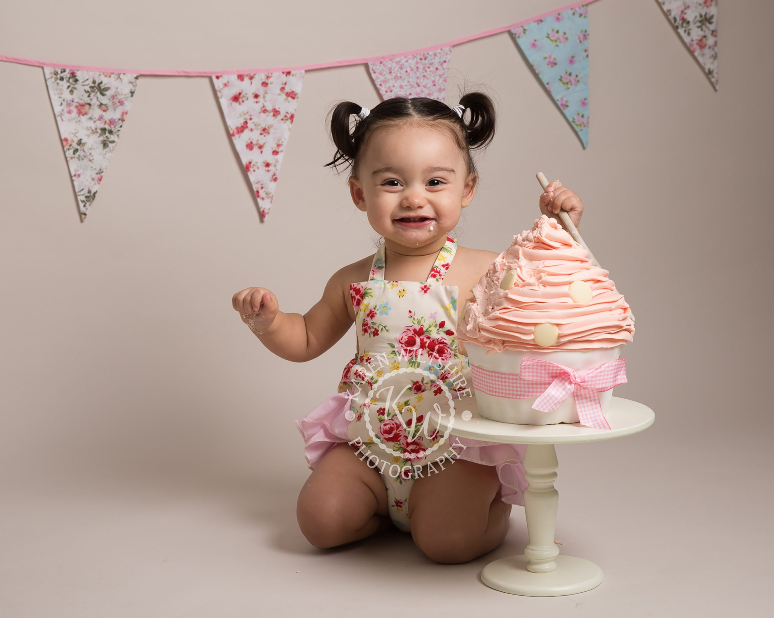 baby girl with pigtail bunches eating large cake