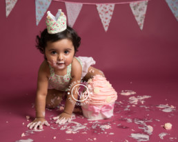Baby girl crawling past a giant cupcake