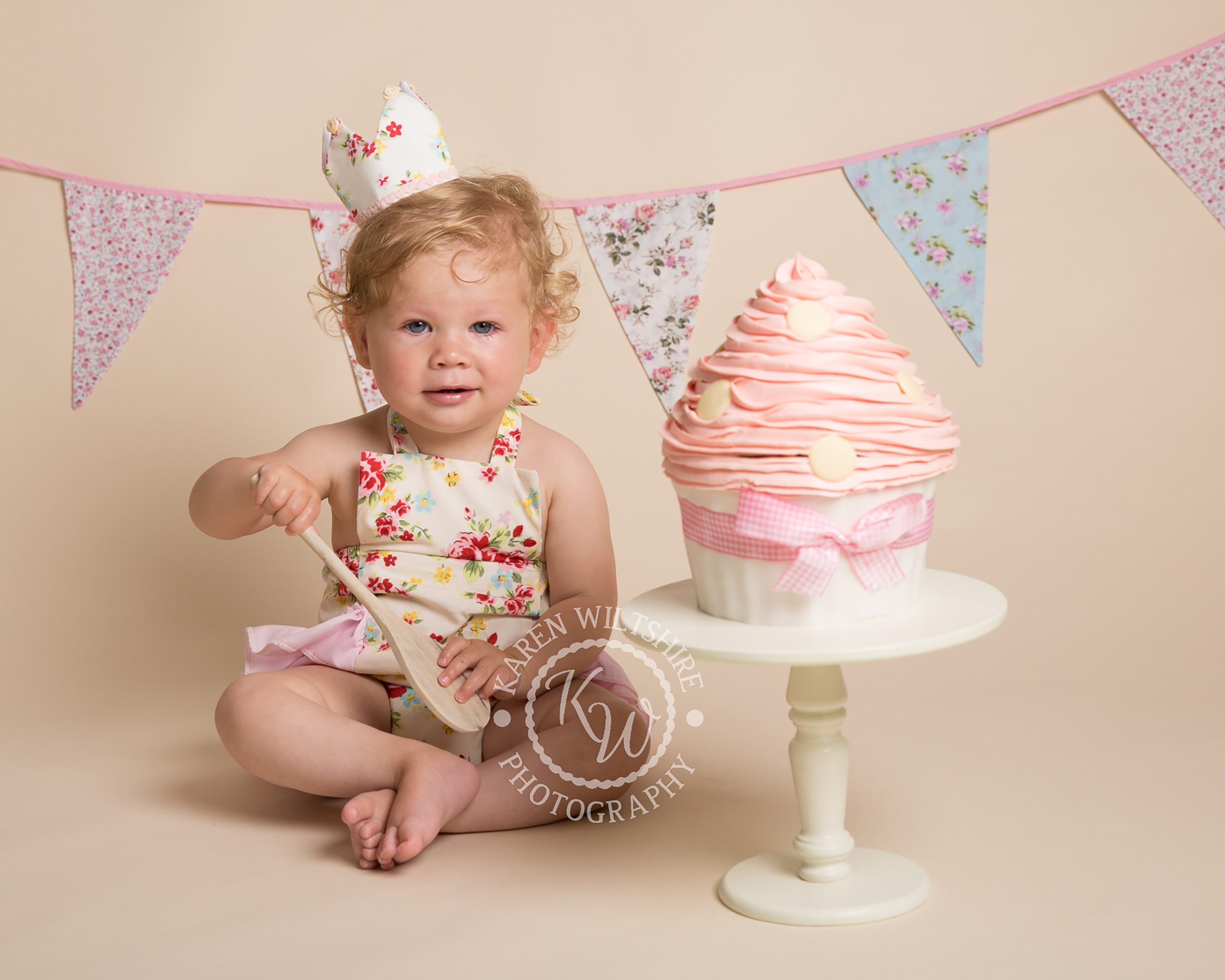 curly haired baby girl ready to smash her cake