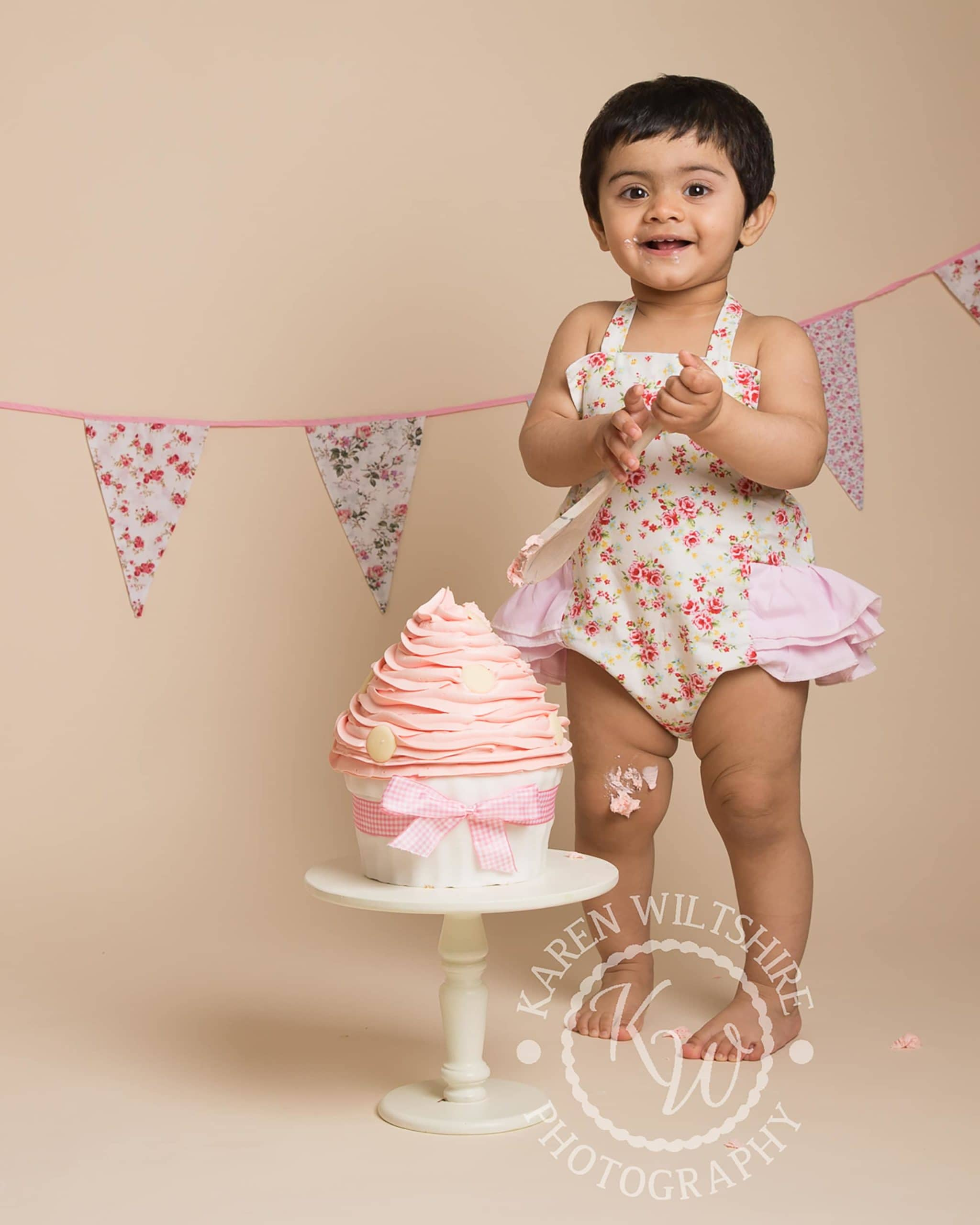 baby girl standing over a pink giant cupcake ready to hit it with a spoon