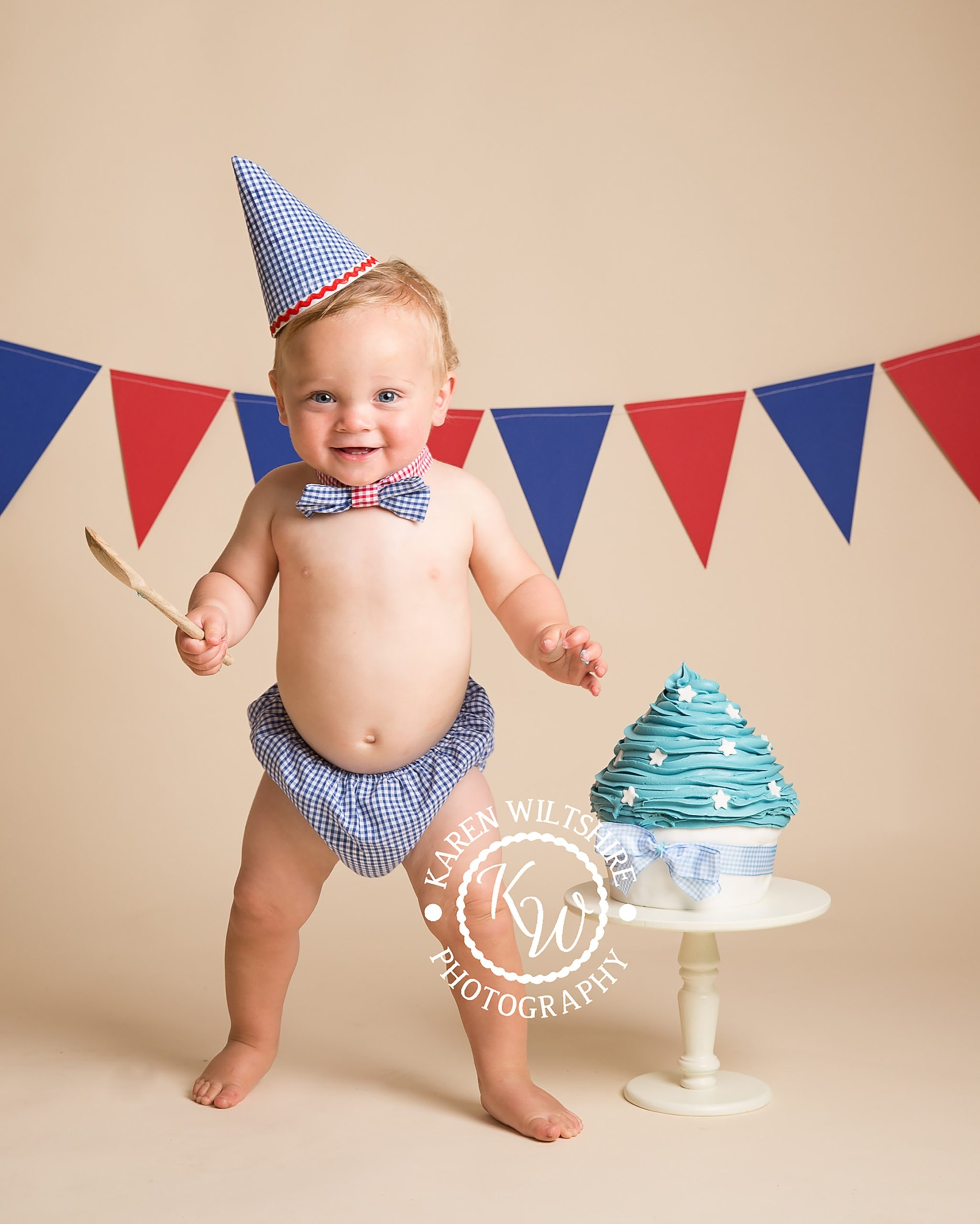 baby boy in blue pants and bowtie smashing a blue cake with a wooden spoon