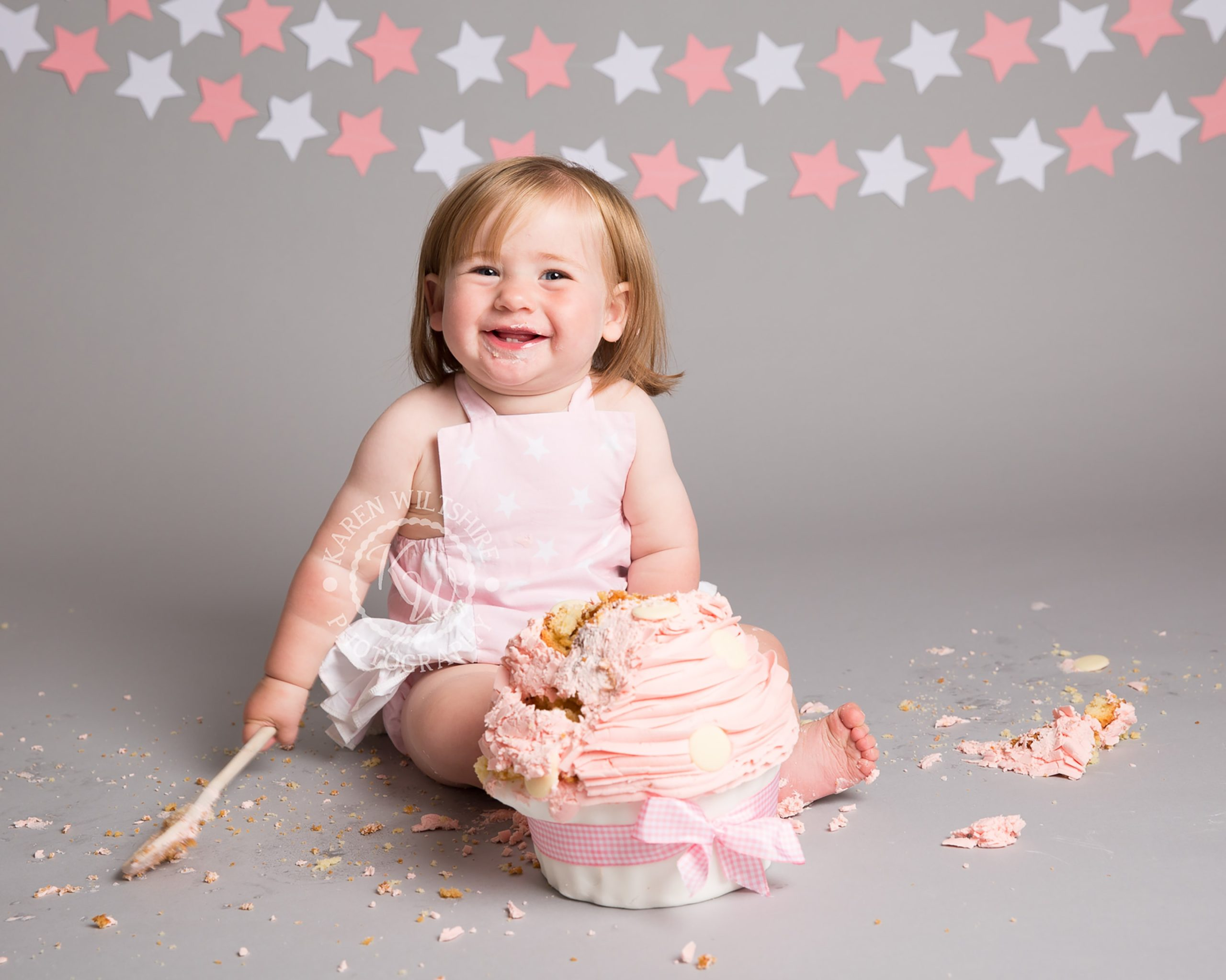 happy baby girl with pink birthday cake