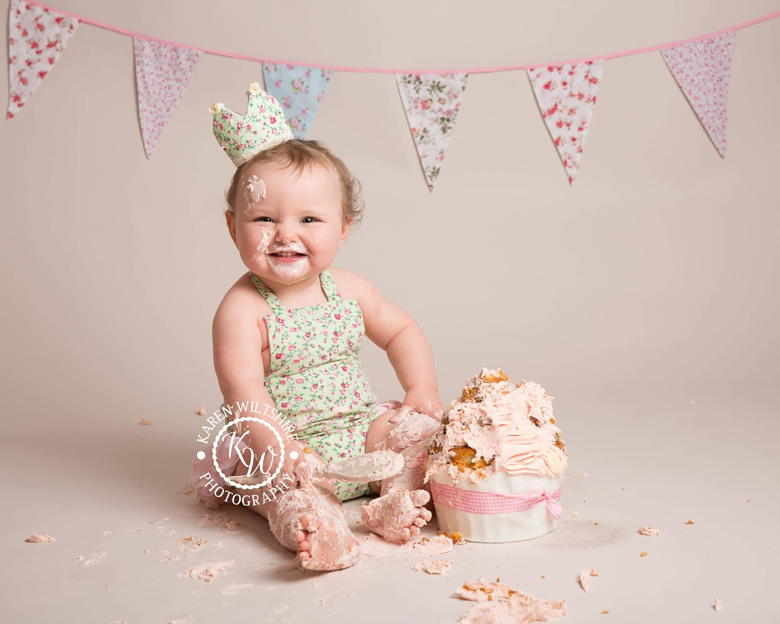 Baby girl smiling at the camera with her birthday cake